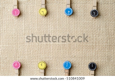 Wooden clothespins on burlap sack background.
