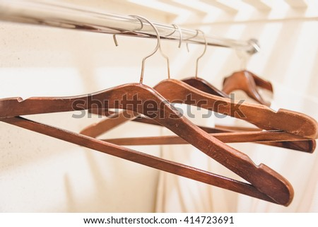wooden coat hangers on clothes rail. -  Warm tone.