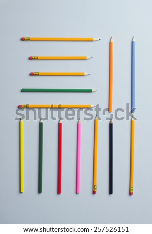 Wooden colored crayons arranged geometrically over blue background - stock photo
