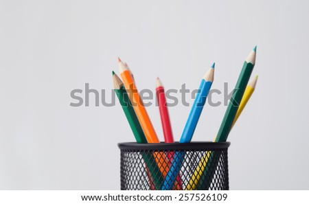 Wooden colored crayons in a pencil box holder over white background