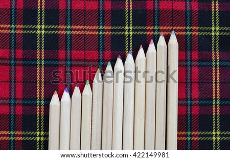 Wooden colorful pencils with sharpening shavings, on red cloth is background. - stock photo