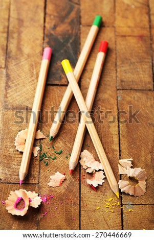 Wooden colorful pencils with sharpening shavings on wooden table - stock photo