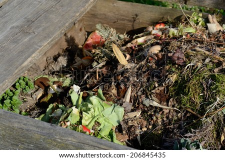 Wooden compost bin with garden and kitchen waste - stock photo