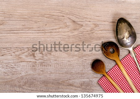 Wooden cooking spoon and silver spoon on a red napkin - stock photo