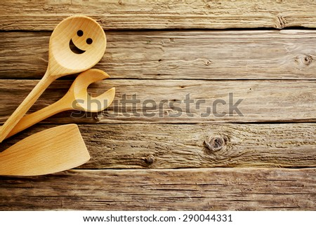 Wooden cooking utensils border on a background of aged weathered vintage wood with a rough rustic texture and plenty of copyspace - stock photo