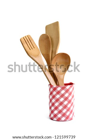 Wooden cooking utensils in container isolated on white
