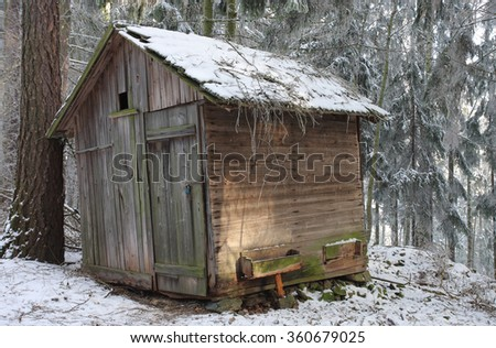 Wooden cottage for hay for feeding of wild animals in snowy forest