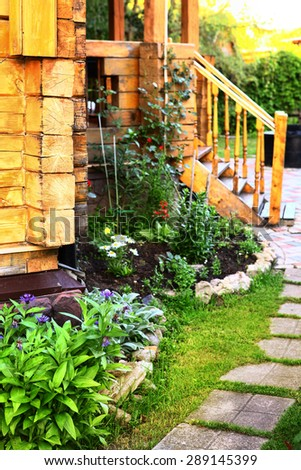 wooden cottage house porch and  tile path in the summer blossoming garden - stock photo