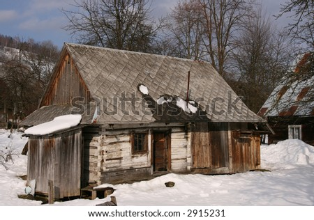 Wooden cottage in Polish countryside. Winter scenery - snow and blue sky. - stock photo