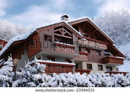 Wooden cottage in the forest covered by snow - stock photo