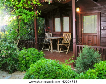 wooden cottage in the garden - stock photo