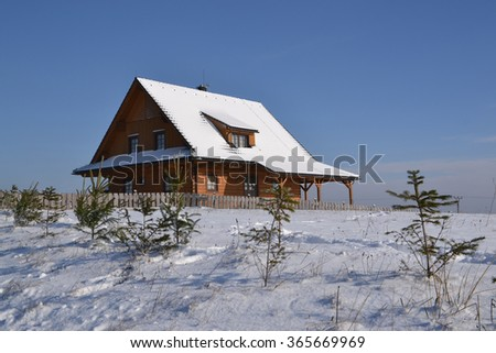 Wooden cottage in the sunny winter day - stock photo