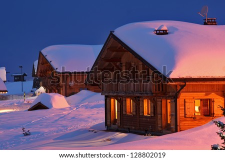Wooden cottage in the winter's evening. - stock photo