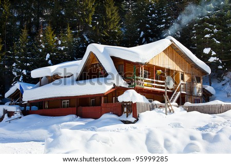 Wooden cottage near the pine forest, covered in snow - stock photo