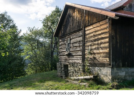 Wooden cottage on green hill in sunny autumn afternoon - Nobody - stock photo