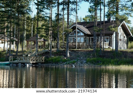 Wooden cottage on the shore of lake - stock photo