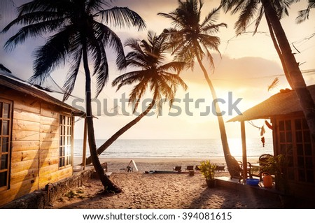 Wooden cottage with sea view in tropical resort with curved coconut palm trees and sunbed on the beach at beautiful sunset - stock photo