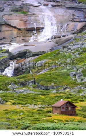 wooden cottage with waterfall in wild nature - stock photo