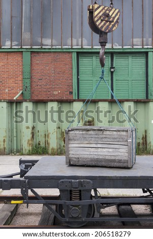 Wooden crate being lifted by crane from freight train car. - stock photo