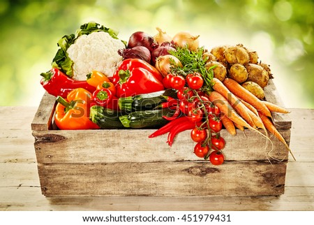 Wooden crate filled with an assortment of healthy farm fresh vegetables on a rustic table outdoors - stock photo
