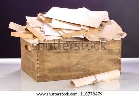 Wooden crate with papers and letters on purple background