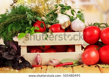 Wooden crate with tomatoes, herbs and spices on a background of the kitchen.