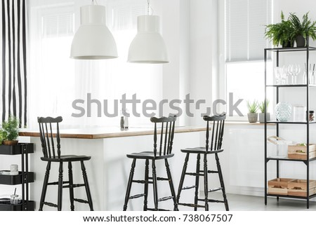 Wooden Crates And Fern On Shelf In White Dining Room With Black Bar Stools At Kitchen