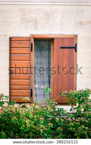 wooden Croatian window in stone wall and plants