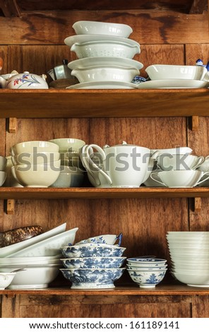 Wooden crockery in the pantry in the kitchen. - stock photo