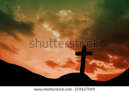 Wooden cross against sky and mountains