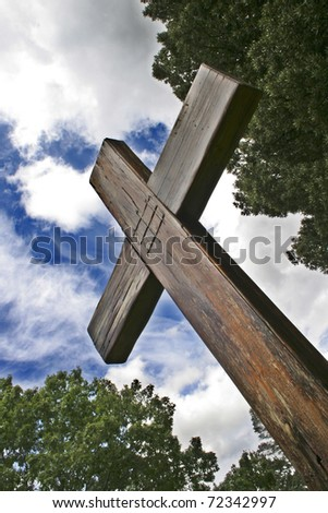 Wooden cross against treetops and cloudy blue sky - stock photo