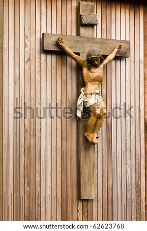 Wooden cross and carving of Jesus being crucified on the cross. - stock photo