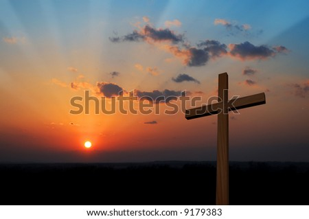 Wooden cross at sunset with colorful clouds
