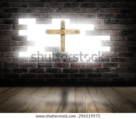 Wooden cross behind a broken brick wall with white light in the background. - stock photo