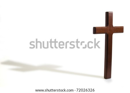 Wooden cross casting a shadow on a white background - stock photo
