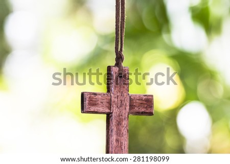 wooden cross hanging against bur nature background - stock photo