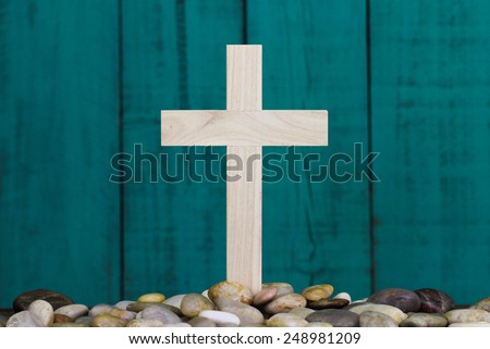 Wooden cross in pile of stones by antique teal blue wood background - stock photo
