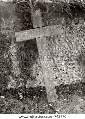 Wooden cross leaning on graveyard stone wall in monochrome - stock photo