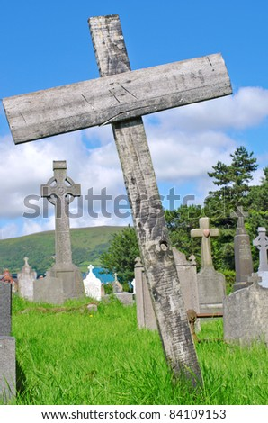 Wooden cross on a grave in the famous landmark Milltown Cemetery Belfast, which is the largest Catholic burial ground in Belfast and synonymous with Irish Republicanism. - stock photo