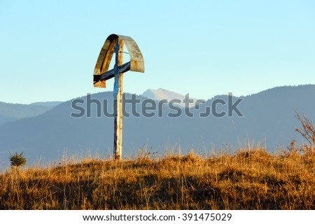 Wooden cross on autumn misty mountain slope.