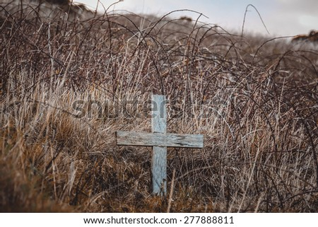 Wooden cross on the hill covered with grey grass and shrubs. - stock photo