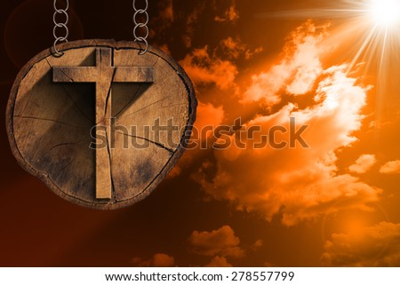 Wooden Cross on Tree Trunk at the Sunset. Wooden Christian cross on a section of tree trunk, hanging from a metal chain at the beautiful sunset with clouds - stock photo