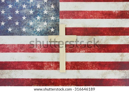 Wooden cross on vintage American flag canvas background - stock photo