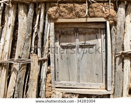 Wooden cross on window of mud church - stock photo