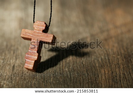 Wooden cross with deep shadow on wooden background - stock photo