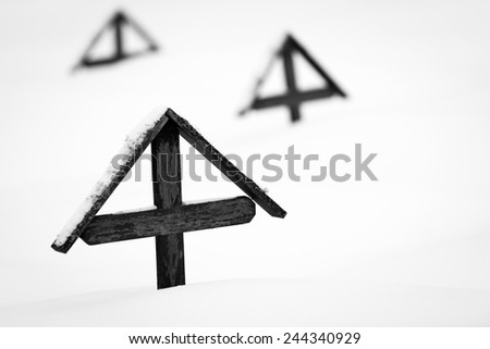 wooden crosses from WWI covered by snow - black and white picture - stock photo