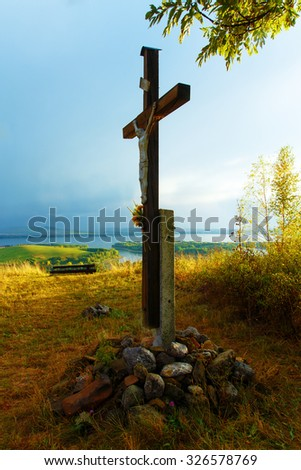 wooden crosses sit upon a hill in the sunset with tree and lake.. - stock photo