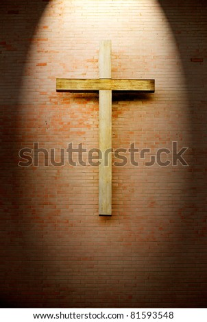 Wooden crucifix on the brick wall lighting by spotlight - stock photo