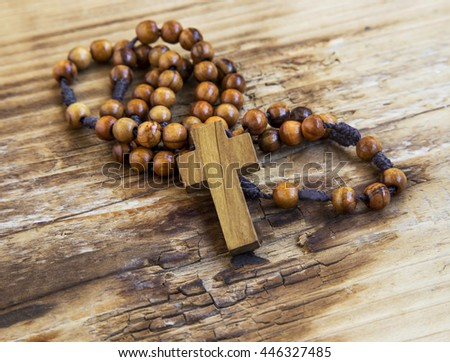 Wooden crucifix with rosary.Christianity symbol on wooden background - stock photo