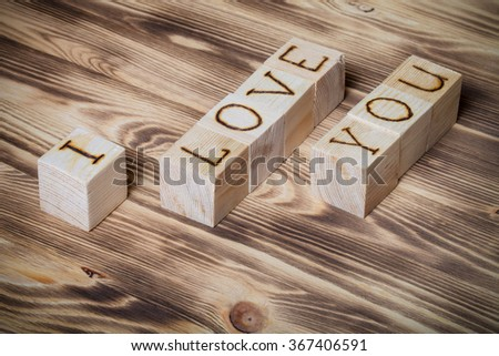 "Wooden cubes with inscription ""I LOVE YOU"" on new wooden background. Toned."